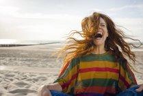 Frau sitzt am Strand und schreit vor Freude — Stockfoto