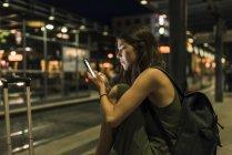 Mujer joven con mochila y equipaje esperando en la estación por la noche usando el teléfono celular - foto de stock