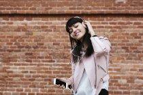 Femme souriante avec téléphone portable écoutant de la musique avec écouteurs contre un mur de briques — Photo de stock