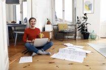 Woman sitting cross-legged on floor of her home, using laptop — Stock Photo