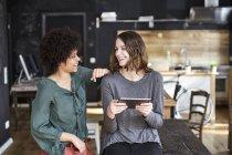 Две смеющиеся молодые женщины с табличкой в офисе — стоковое фото
