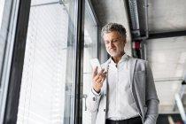 Homme d'affaires mature souriant debout à la fenêtre dans le bureau et tenant un téléphone portable — Photo de stock