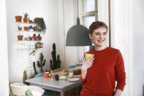 Mujer de pie en su cómoda casa, bebiendo café - foto de stock