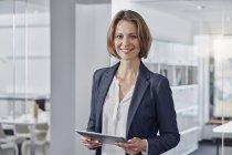 Портрет улыбающейся деловой женщины, держащей планшет в кабинете — стоковое фото