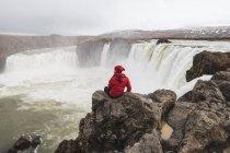 Islanda, uomo seduto alla cascata Godafoss — Foto stock