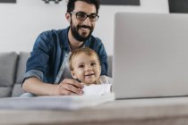 Father and daughter using laptop at home — Stock Photo