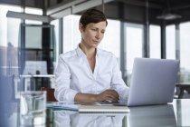 Geschäftsfrau sitzt mit Laptop am Glastisch im Büro — Stockfoto