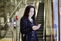 Портрет молодой женщины, смотрящей на мобильный телефон в метро — стоковое фото