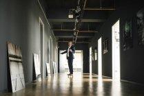 Empresario montando longboard y usando el teléfono celular en el piso de la oficina - foto de stock