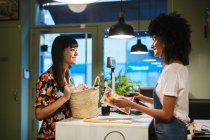 Smiling customer and shop assistant at counter of a store — Stock Photo