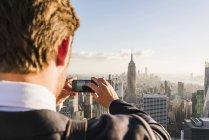 США, Нью-Йорк, мужчина, фотографирующий сотовый телефон на смотровой площадке Рокфеллеровского центра — стоковое фото