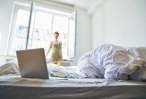 Ordinateur portable sur le lit avec femme debout devant la fenêtre en arrière-plan — Photo de stock