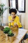 Молодая африканская американка сидит за столом, пьет сок и проверяет смартфон — стоковое фото