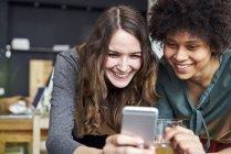 Две улыбающиеся молодые женщины делят мобильный телефон в офисе — стоковое фото