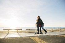 Padre e figlio in sella scooter sul lungomare al tramonto — Foto stock