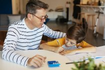 Father watching son doing homework at table at home — Stock Photo