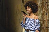 Портрет модной молодой женщины с вьющимися волосами по телефону — стоковое фото