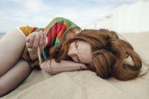 Donna dai capelli rossi sdraiata sulla spiaggia, con la sabbia che le scorre tra le mani — Foto stock