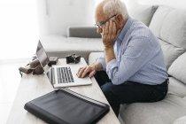 Uomo anziano utilizzando computer portatile, vecchia macchina fotografica — Foto stock