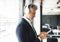 Hombre de negocios maduro de pie en la ventana en la oficina con auriculares y teléfono celular - foto de stock