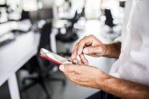 Mani di uomo d'affari utilizzando il cellulare in ufficio — Foto stock