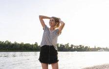 Jeune femme marchant au bord de la rivière le soir — Photo de stock