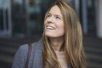 Retrato de mulher de negócios sorridente assistindo algo — Fotografia de Stock