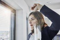 Giovane donna d'affari fiduciosa che guarda fuori dalla finestra in ufficio — Foto stock