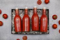 Ряд з чотирьох крижаний гойдалки Top пляшки з домашнім томатним соком — стокове фото