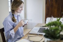 Smiling woman sitting at desk with cup of coffee and laptop — Stock Photo