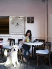 Young woman sitting in a coffee shop with her dog and drinking a smoothie — Stock Photo