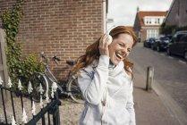 Mulher ruiva usando fones de ouvido na cidade — Fotografia de Stock