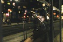 Mujer joven con auriculares esperando en la estación por la noche utilizando la tableta - foto de stock