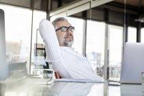 Empresário com laptop na mesa no escritório pensando — Fotografia de Stock