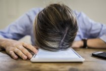 Close-up of woman lying on tablet at desk — Stock Photo