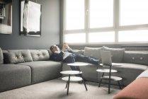 Зрелый бизнесмен лежит на диване с помощью мобильного телефона — стоковое фото