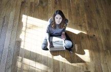 Портрет молодой женщины с ноутбуком на деревянном полу — стоковое фото