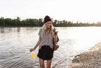 Young woman walking barefoot on riverside, earphones and smartphone — Stock Photo