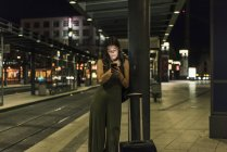 Young woman waiting at the station by night using cell phone — Stock Photo