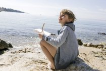 Boy sitting at seaside with self-made toy boat — Stock Photo
