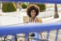 Portrait de jeune femme souriante aux cheveux bouclés sur un pont — Photo de stock