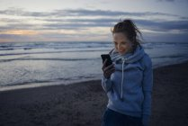 Woman using smartphone on the beach at sunset — Stock Photo