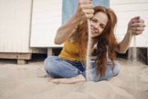 Redheaded woman sitting in front of beach cabin, with sand trickling through her hands — Stock Photo