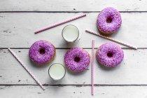 Чотири рожеві пончики, два склянки молока і соломинки на білому дереві — стокове фото
