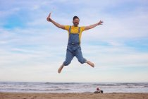 Portrait of happy man in dungarees jumping with soda in hand on the beach — Stock Photo
