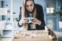 Женщина-архитектор фотографирует архитектурную модель в офисе — стоковое фото