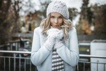 Портрет улыбающейся женщины в шерстяной шляпе, перчатках и шарфе — стоковое фото