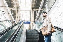 Молода людина з скейтбордом і навушниками на ескалаторі на вокзалі — стокове фото