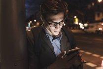 Uomo d'affari che usa il cellulare sulla strada urbana di notte — Foto stock