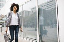 Mujer sonriente con bolso y smartphone caminando al aire libre - foto de stock